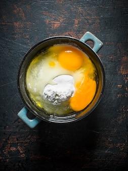 Meel met eieren in de pan op donkere rustieke tafel.