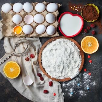 Meel met eieren, sinaasappel, melk, cacao, klop in een kom op stenen oppervlak