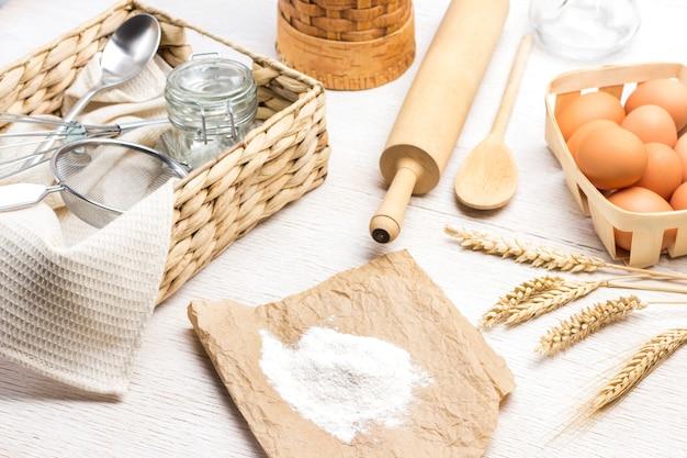 Meel op papier. aartjes van tarwe. eieren in rieten doos en aartjes van tarwe. glazen pot, zeef en lepel in rieten doos. witte achtergrond. bovenaanzicht