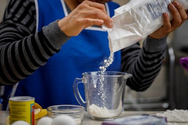 Meel toevoegen aan een maatbeker om een bananenpannenkoek te maken thuisbakconcept