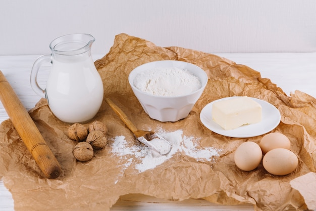 Meel; walnoten; eieren; kaas; deegroller op bruin verfrommeld papier