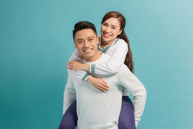 Meeliften. jonge man met vriendin op zijn rug, blauw met kopie ruimte.