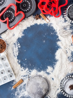 Meelkader bakconcept op donkerblauw met gereedschapstoebehoren en zoetekauwgebak koekjetaart ingrediënten suiker, eieren, cacao, kaneel. de hoogste meningsvlakte legt makend deegconcept