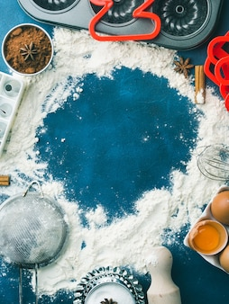 Meelkader bakkersconcept achtergrond op donkerblauw met gereedschapstoebehoren en zoet voedsel koekje taart ingrediënten ingrediënten suiker, eieren, cacao, kaneel. de hoogste meningsvlakte legt makend deegconcept