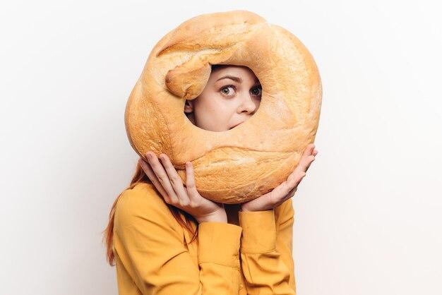 Meelproduct rond brood en emotionele vrouw in een geel overhemd op een lichte muur.