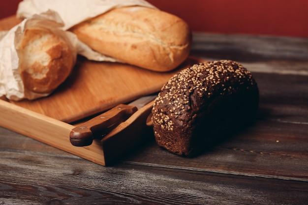 Meelproducten roggebrood op een dienblad en een scherp mes op tafel. hoge kwaliteit foto