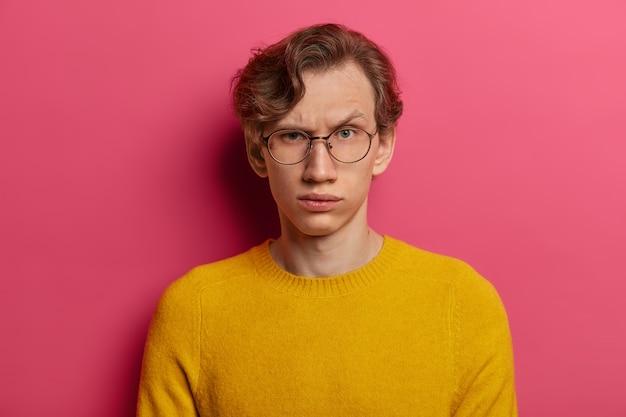 Meen je het? de streng verontwaardigde man trekt wenkbrauwen op, twijfelt, is niet zeker, geconcentreerd met een twijfelachtige blik, draagt een ronde doorzichtige bril en een gele trui. uitdrukkingen van het menselijk gezicht