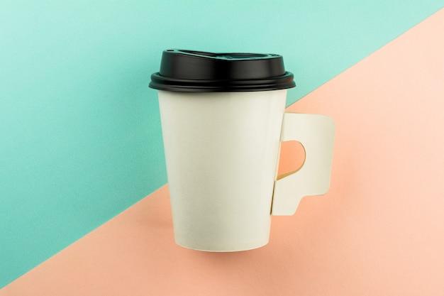 Meeneemdocument koffiekop op blauwe en roze achtergrond.