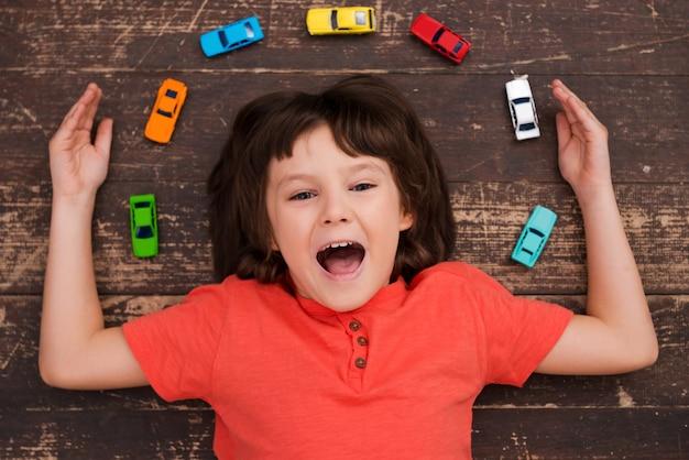 Meer auto's meer vreugde! bovenaanzicht van een kleine jongen die op de grond ligt en naar de camera kijkt en glimlacht