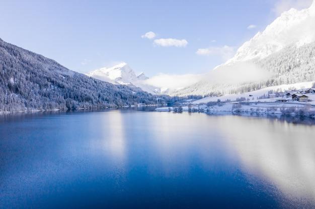 Meer bij de met sneeuw bedekte heuvels, vastgelegd op een zonnige dag