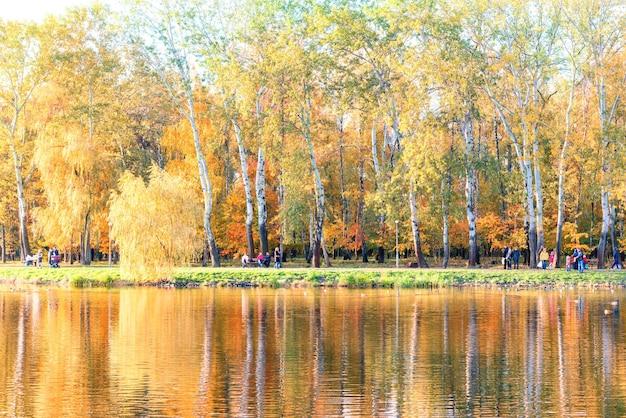 Meer in het herfststadspark met kleurrijke bomen en wandelende mensen