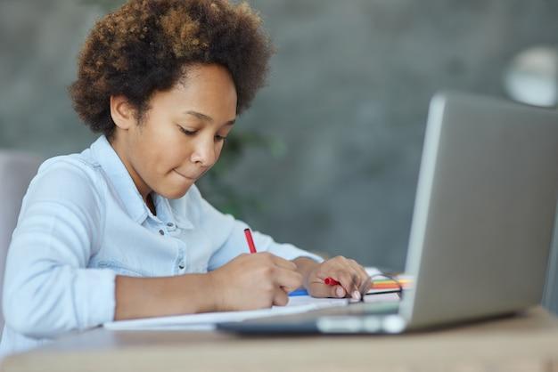 Meer informatie portret van een tienerschoolmeisje dat markeringen gebruikt terwijl ze haar huiswerk maakt met een laptop