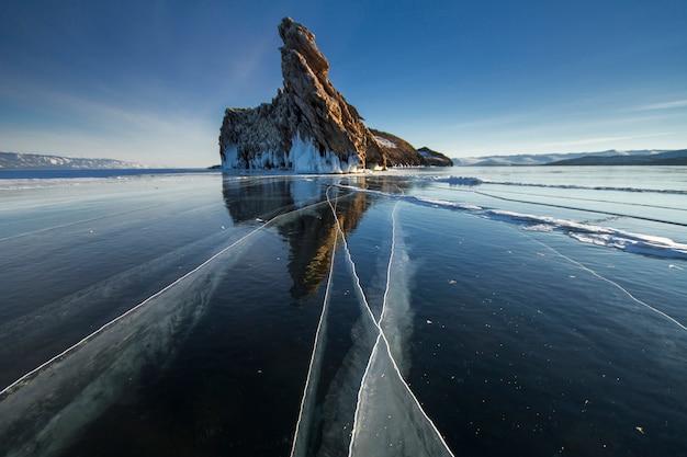 Meer is bedekt met een dikke laag ijs. steen rots
