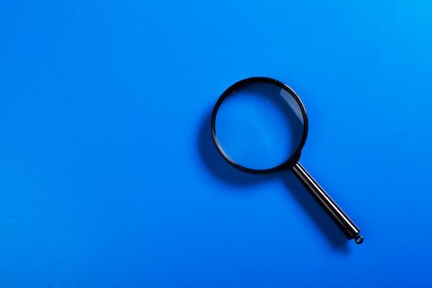 Meer magnifier op blauwe achtergrond dicht omhoog
