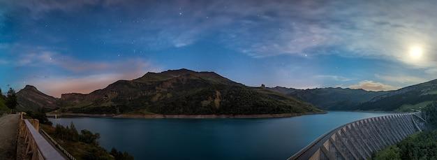 Meer met bergen tijdens blauw uur in de franse alpen