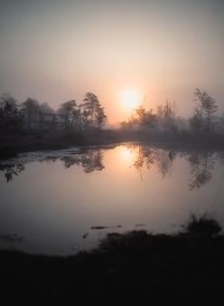 Meer met weerspiegeling van de zon met bomen eromheen tijdens zonsondergang