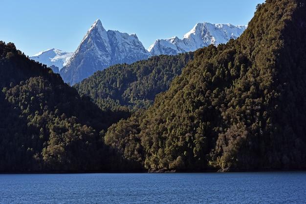 Meer omgeven door bossen en rotsachtige bergen bedekt met de sneeuw
