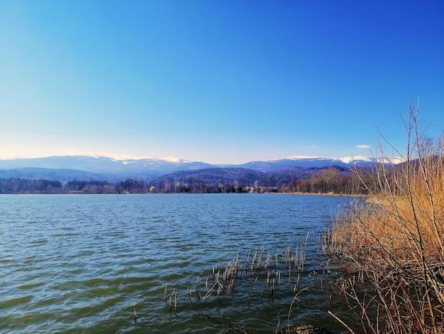 Meer omgeven door heuvels en gras in het zonlicht en een blauwe lucht in polen
