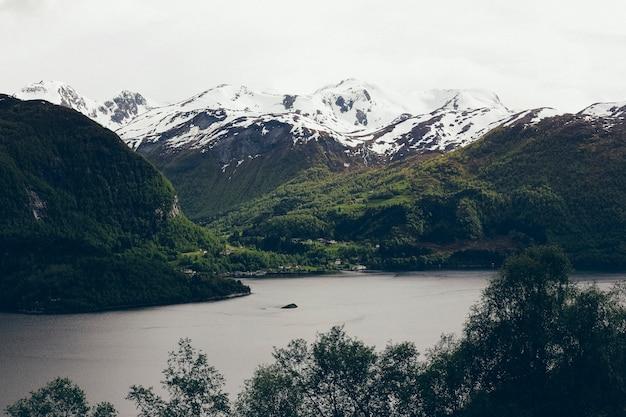 Meer omgeven door hoge besneeuwde bergen in de winter.