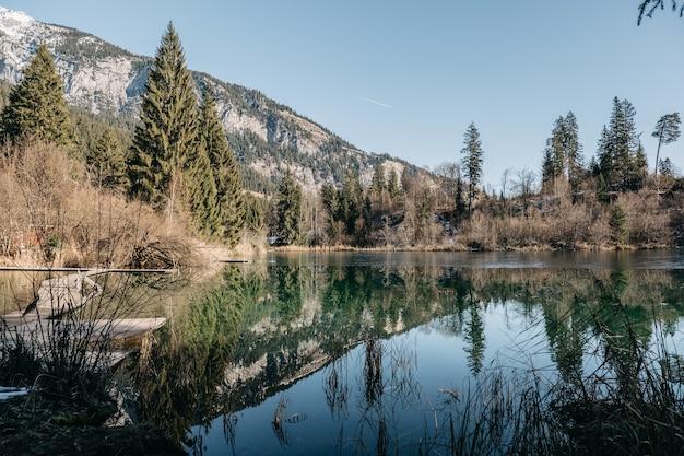 Meer omgeven door rotsen en bossen met bomen die reflecteren op het water onder het zonlicht