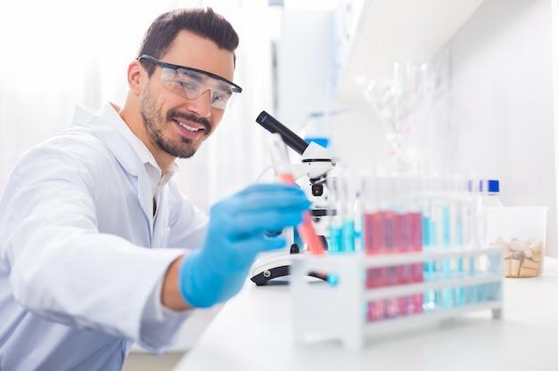 Meer voorbeelden. vrolijke homo-mannelijke laboratoria grijnzend terwijl ze een flesje pakken en een veiligheidsbril opzetten