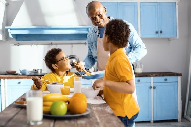 Meer willen. aangename jongen die een ander gerecht aan zijn zonen aanbiedt en bewonderend naar hen glimlacht terwijl ze aan het ontbijten zijn