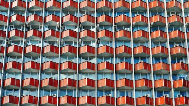 Meerdere identieke balkons en ramen op de gevel van een oud sovjetgebouw