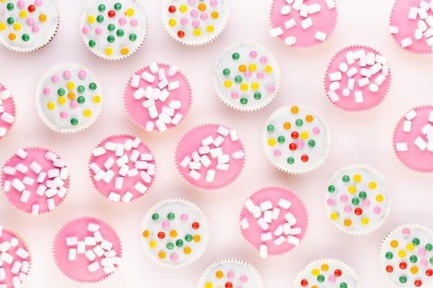 Meerdere kleurrijke mooi ingerichte muffins op een witte achtergrond, bovenaanzicht.