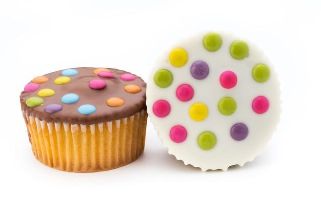 Meerdere kleurrijke versierde muffins op een witte achtergrond.