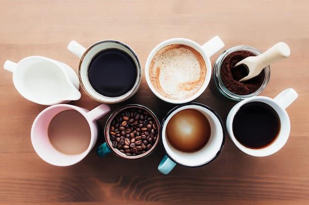 Meerdere koffiekopjes en veelkleurige mokken met americano, espresso, latte en cappuccino, melkpot, gebrande koffiebonen in glazen fles, houten lepel en gemalen koffie in pot op houten achtergrond