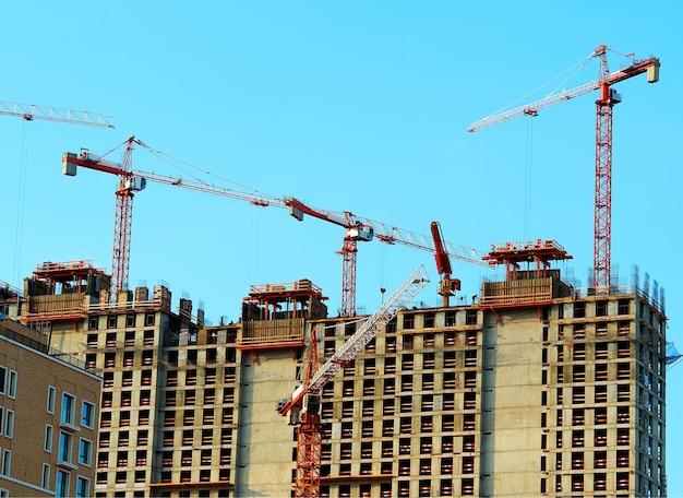 Meerdere kranen die de achtergrond van moderne gebouwen bouwen