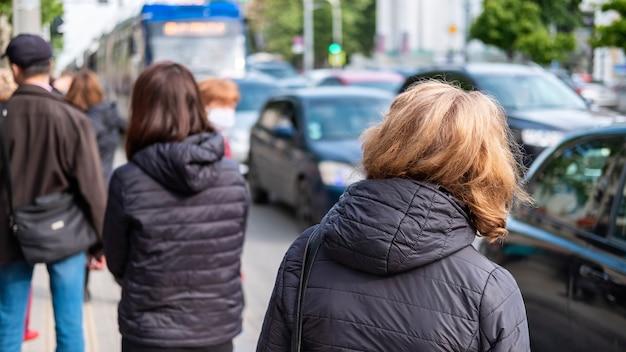 Meerdere mensen wachten op het transport op een station, auto's op de weg