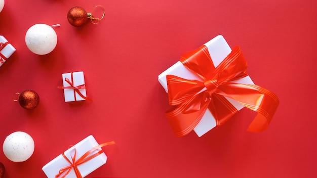 Meerdere witte geschenkdozen met rode banden en kerstversiering