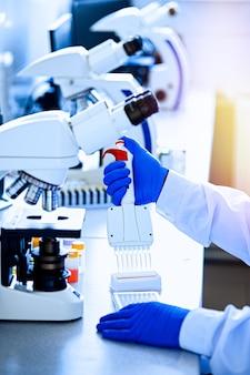Meerkanaalspipet met variabel volume. medisch werker, wetenschapper, laboratoriumassistent in rubberen handschoenen werkt in het laboratorium