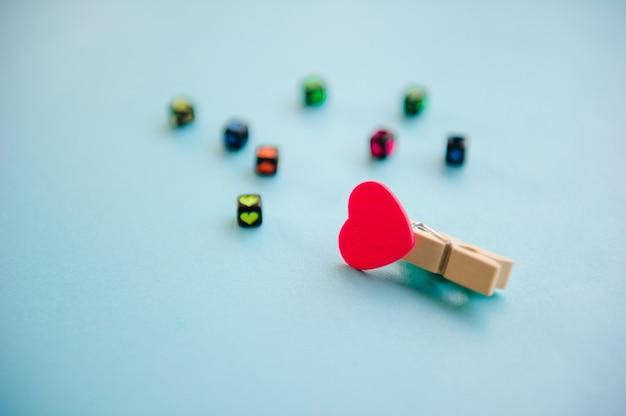 Meerkleurige houtklemmen in hartvorm op pastel lichtblauwe achtergrond