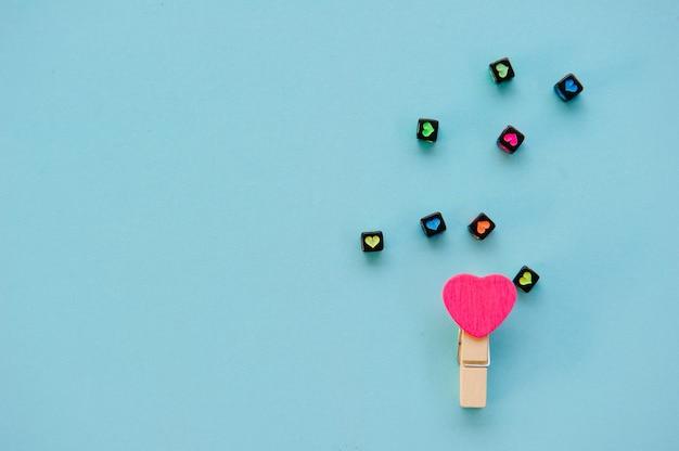 Meerkleurige houtklemmen in hartvorm op pastelkleurige lichtblauwe achtergrondvalentijnsdag met zoete en