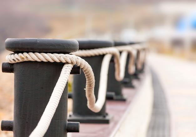 Meerpalen met touwen op een kade voor decoratief hekwerk.