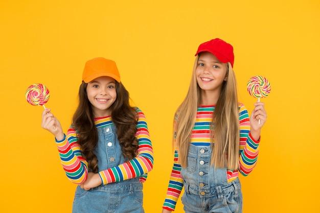 Meest verleidelijke suikerhoudende gerechten. kleine meisjes houden lolly's op stokken op gele achtergrond. kleine kinderen genieten van ongezond eten. dessert eten. eten of lekkers.