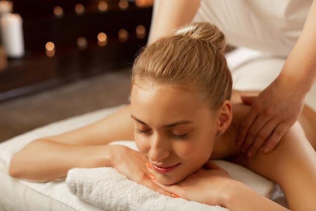 Meester handelen. rustige jonge vrouw die spa-centrum bezoekt en een ontspannende massage krijgt in een uitgeruste kast