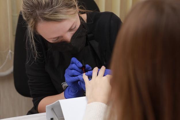 Meester in beschermend masker en handschoenen tijdens een manicure bij schoonheidssalon