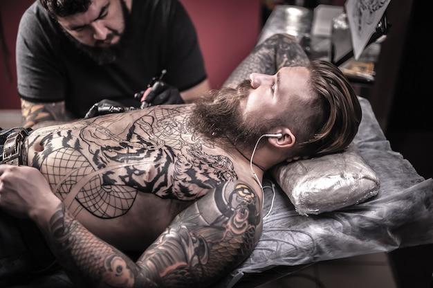 Meester in de kunst van het tatoeëren, het maken van een tatoeage op zijn cliënt, een atelierstudio
