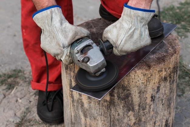 Meester in een rode overall met handen in werkhandschoenen maalt een stuk staal