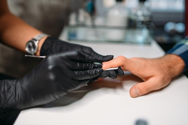 Meester in handschoenen die spijkers oppoetsen aan mannelijke cliënt