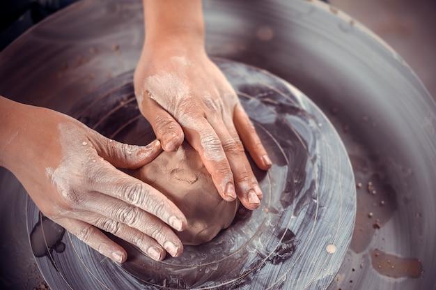 Meester-keramist maakt een aarden pot op een pottenbakkersschijf