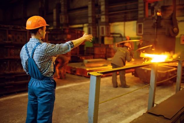 Meester kijkt naar staalproductieproces in oven, staalfabriek, metallurgische of metaalverwerkende industrie, industriële productie van metaalproductie op molen