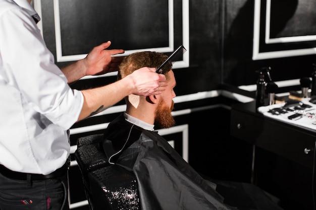 Meester knipt haar en baard in de kapperszaak. kapper maakt kapsel met een schaar en een metalen kam