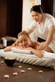 Meester massage. stralende knappe dame liggend op een matras en genietend van de procedure terwijl de meester haar schouders verwerkt