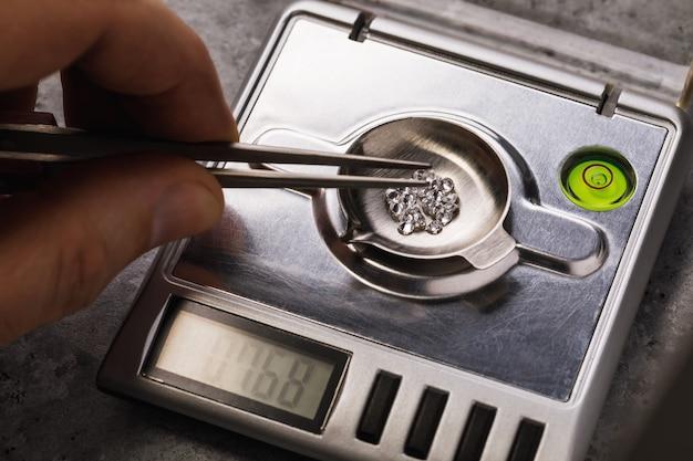 Meester meet het gewicht van edelstenen op sieradenweegschalen