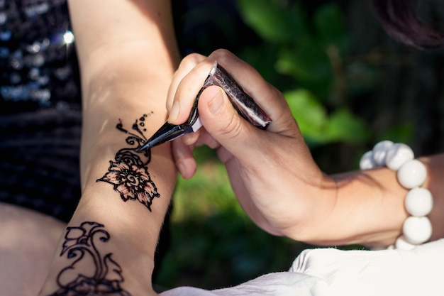 Meester mehndi tekent henna op een vrouwelijke hand