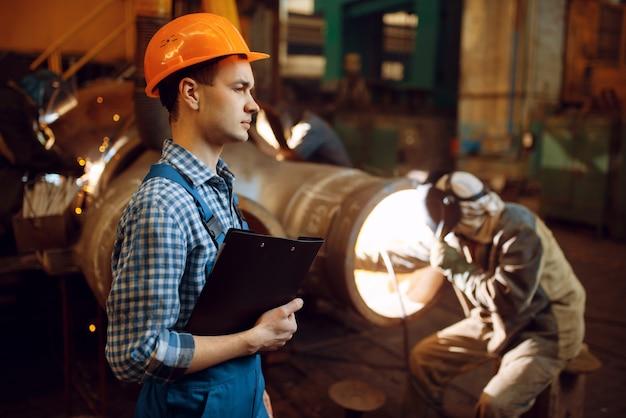 Meester met notitieboekje en lasser op fabriek